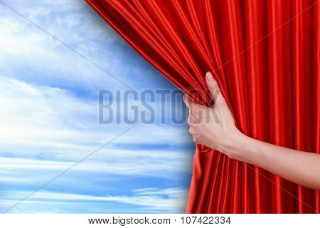 Human hand opens red curtain on sky background