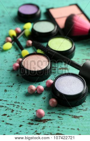 Make up powder and brushes on wooden table closeup