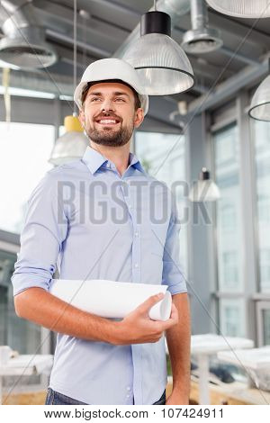 Attractive male engineer with the hardhead in office
