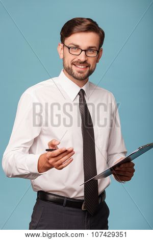 Attractive young businessman is working with papers