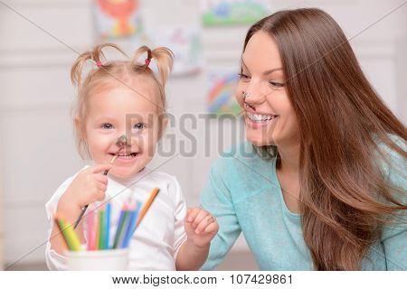 Pretty young woman is teaching her child to draw