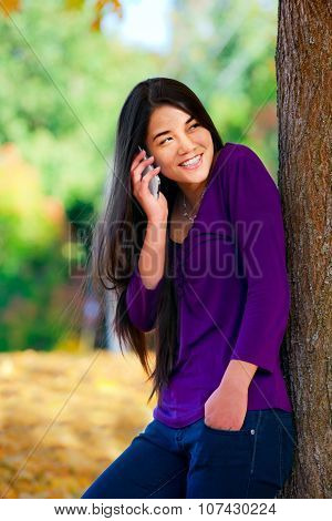 Teen Girl Standing Against Autumn Tree Talking On Cell Phone