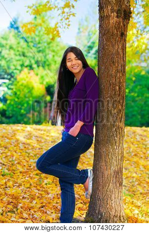 Biracial  Teen Girl Leaning Against Tree, Autumn Leaves On Ground
