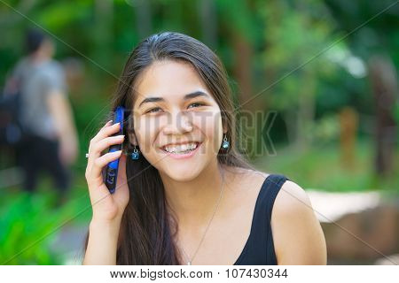 Biracial Teen Girl Talking On Cell Phone Outdoors