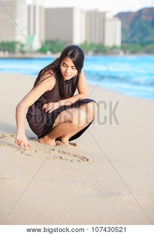 Biracial Teen Girl On Waikiki Beach Drawing In The Sand