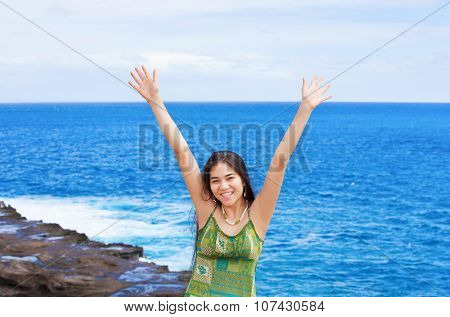 Biracial Teen Girl Arms Raised By Ocean Water In Praise