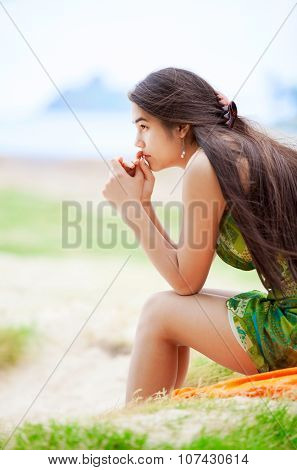 Beautiful Biracial Teen Girl Sitting At Tropical Beach, Praying
