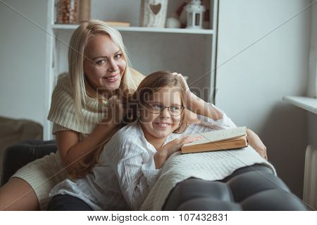 Mother with daughter reading book