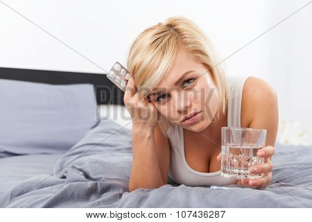 sick woman with pack of pills lying on bed