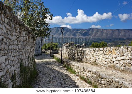 stone walls of old fortress and mountains in background, Berat, Albania