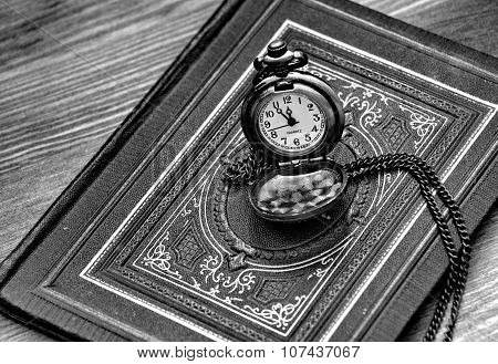 retro pocket watch lying on the old book with ornaments, in black and white