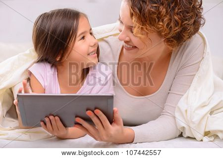 Happy mother and daughter surfing the Internet