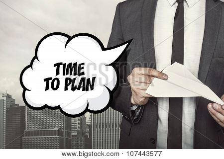 Time to plan text on speech bubble with businessman holding paper plane in hand