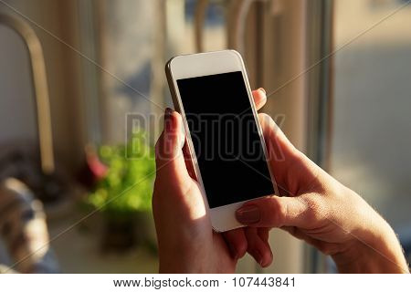 Woman Hands Holding A Smart Phone At Home With A Windows Background.