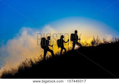Silhouettes of three people walking with backpacks