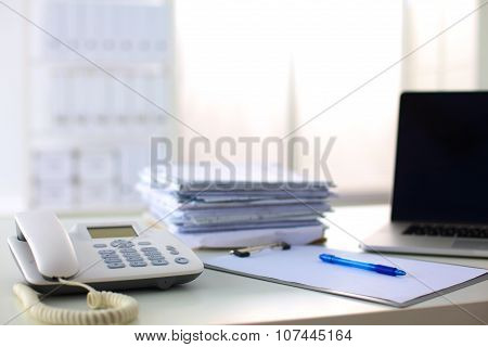 Laptop with stack of folders on table on white background