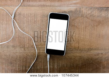 Smartphone with earphone on wooden table