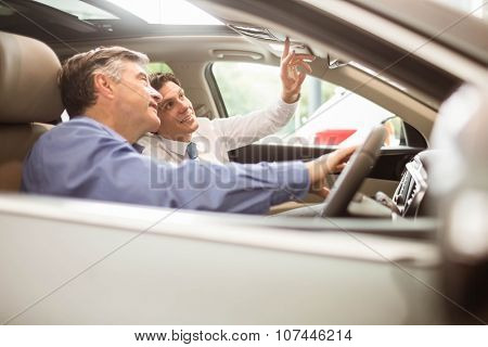 Businessman pointing a car interior at new car showroom