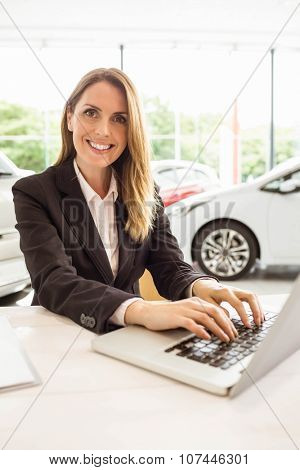 Smiling saleswoman typing on her laptop at new car showroom