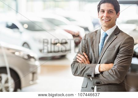 Smiling businessman standing with arms crossed at car showroom