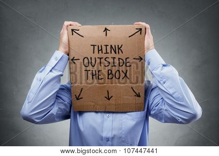 Businessman with cardboard box on his head saying think outside the box concept for brainstorming, creativity, innovation, strategy or individuality