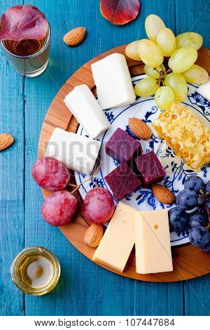 Cheese plate with fresh grape, honey, nuts,plum jelly, marmalade