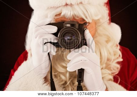 Portrait of santa taking a photo against room with wallpaper