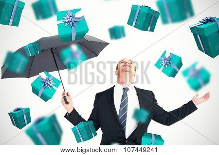 Businessman sheltering under black umbrella testing against blue and silver presents