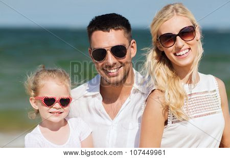 family,  vacation, adoption and people concept - happy man, woman and little girl in sunglasses on summer beach