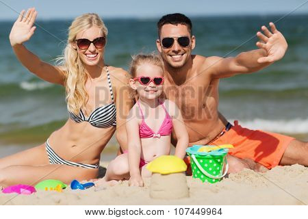 family, travel, vacation and people concept - happy man, woman and little girl in sunglasses with sand toys waving hands on summer beach