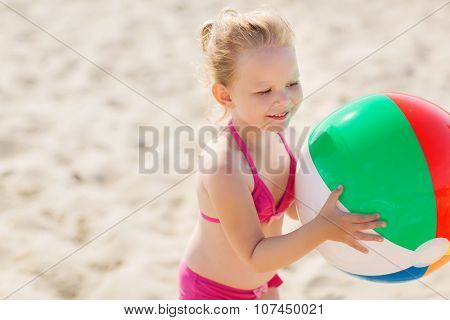 summer, childhood, vacation and people concept - happy little girl playing with inflatable ball on beach