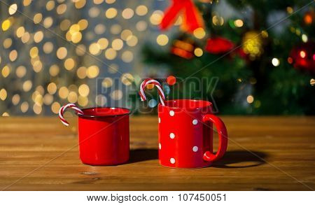 holidays, christmas, winter, food and drinks concept - close up of candy canes and cups on wooden table over lights