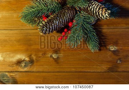 christmas decoration, holidays, new year and decor concept - close up of natural fir branch and fir-cone on wooden table