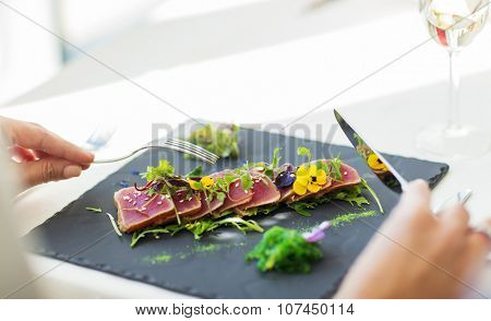 people, holidays, celebration and lifestyle concept - close up of woman eating salad appetizer for dinner at restaurant