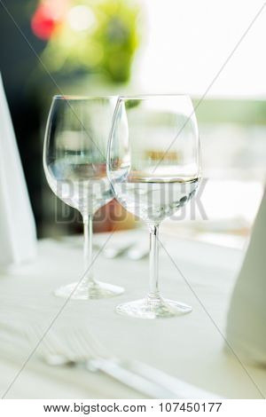 glassware and objects concept - close up of two wine glasses on restaurant table