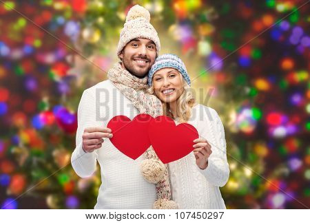 love, valentines day, couple, christmas and people concept - smiling man and woman in winter hats and scarf holding red paper heart shapes over holidays lights background
