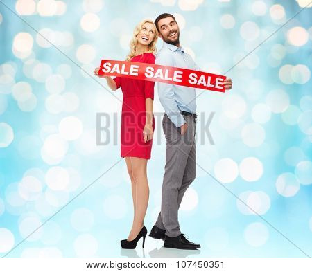 people, sale, discount and holidays concept - happy couple with red sale sign standing back to back over blue holidays lights background