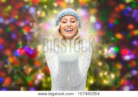 winter, magic, christmas and people concept - smiling young woman in hat and sweater holding fairy dust on her palms over lights background