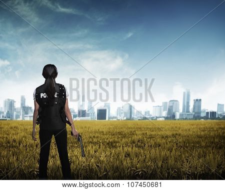 Police Woman Looking The City In The Middle Of Field