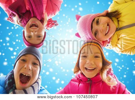 childhood, friendship, winter, christmas and people concept - happy little children faces outdoors over blue sky and snow background