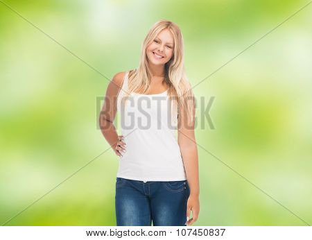 people, holidays, style and body type concept - smiling young woman in blank white shirt and jeans over green natural background