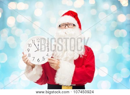 christmas, holidays, time and people concept - man in costume of santa claus with clock showing twelve over blue holidays lights background