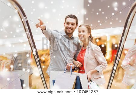 sale, consumerism and people concept - happy young couple with shopping bags raising on escalator and pointing finger in mall with snow effect