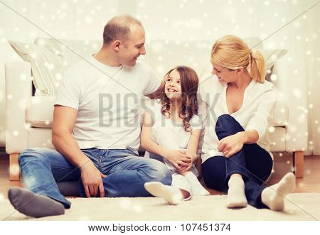 family, childhood, communication, people and home concept - smiling parents with little girl sitting on floor at home