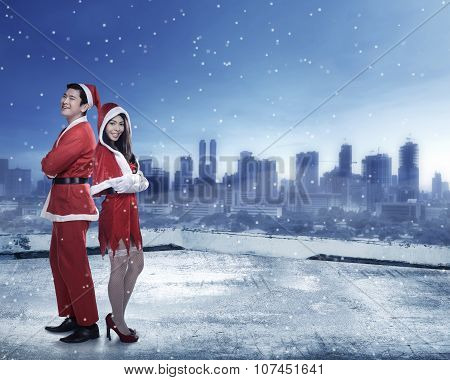 Happy Couple In Santa Claus Costume Standing On The Building Rooftop