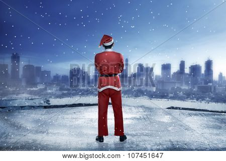 Asian Man Wearing Santa Claus Costume Standing On The Building Rooftop