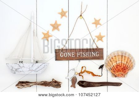 Abstract nautical background with gone fishing sign, driftwood, starfish and scallop shells, seaweed and decorative wooden boat over white wood.