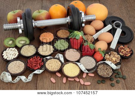 Body building dumbbells and hand grippers with health and super food selection including supplement powders  and fresh fruit with tape measure over oak background.