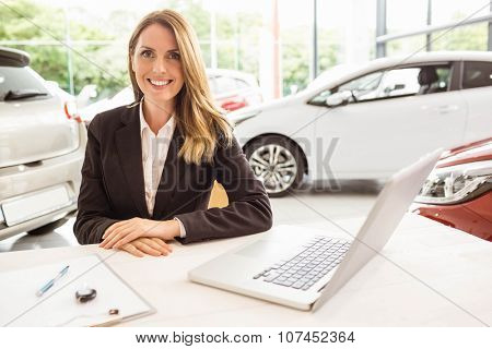 Smiling saleswoman behind her desk at new car showroom