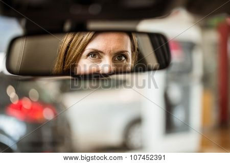 Young woman in the drivers seat looking in the mirror at new car showroom